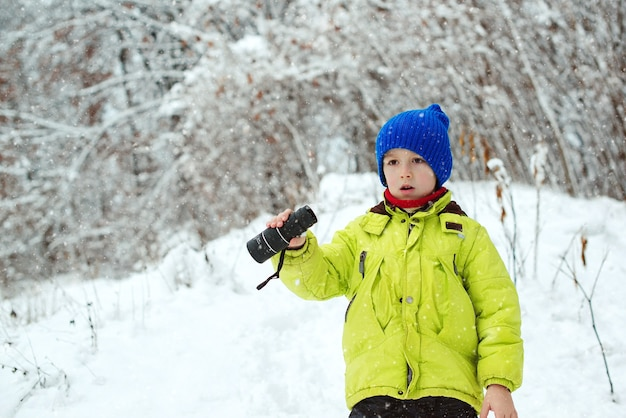 Family vacation, snowy day and happy childhood. happy child walking at winter forest. kid looking to monocular. family winter holidays. winter fun at nature. cute child explorer in snowy forest.