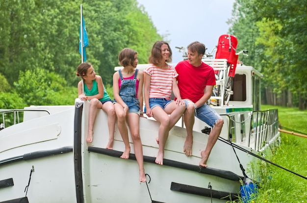 Family vacation, summer holiday travel on barge boat in canal, happy kids and parents having fun on river cruise trip in houseboat in france