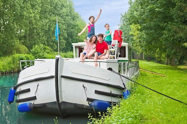 Семейные каникулы, летние каникулы, путешествия на барже по каналу, счастливые дети и родители веселятся