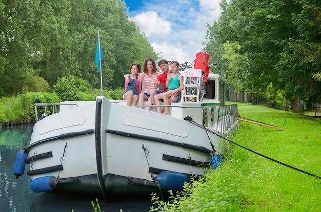 Семейный отдых, летние каникулы, путешествие на барже в канале, счастливые дети и родители