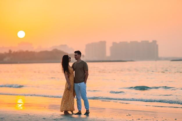 Семейный отдых. молодая пара на пляже на закате в оаэ