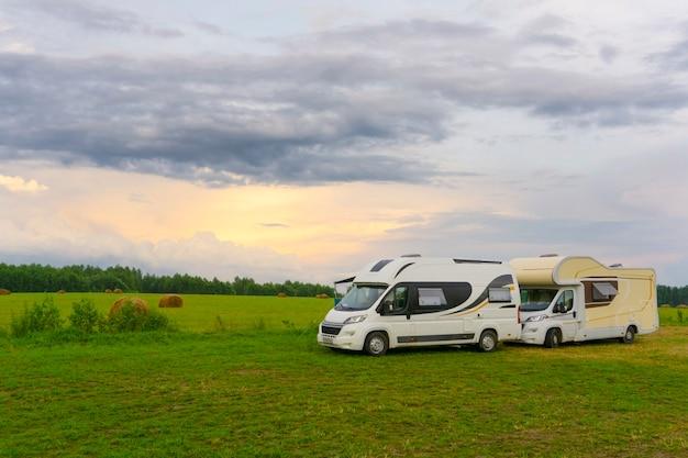 家族での休暇とキャンピングカー(キャラバン車)での屋外旅行(旅行)。屋外のサマーキャンプで2つのキャンピングカー。車のコンセプトで旅行(旅行)。