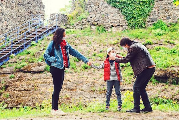 Семейный отдых во время пандемии коронавируса. семья гуляет возле руин замка.