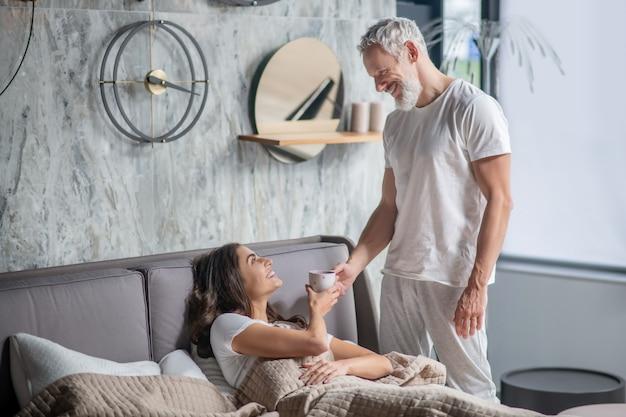 Семейные ценности. любящий заботливый красивый седой муж держит кофе лежащей радостной жене дома в спальне