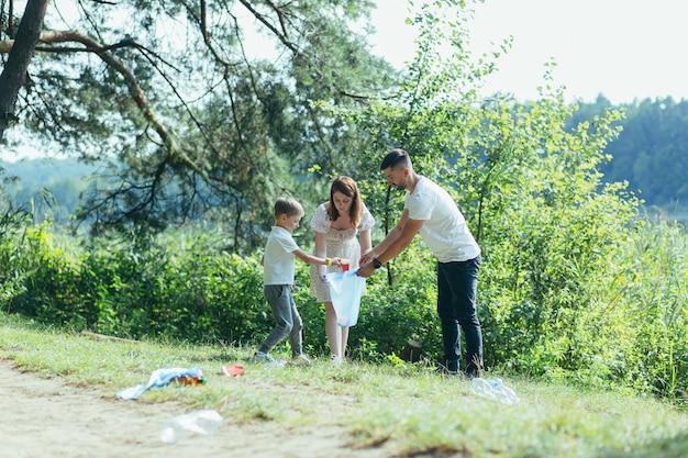 家族のボランティアが自然の中でゴミを掃除します。父と母、両親、子供、息子の家族が晴れた日にボランティアで、ビニール袋に折りたたまれたがれきの森のゴミ箱を掃除します