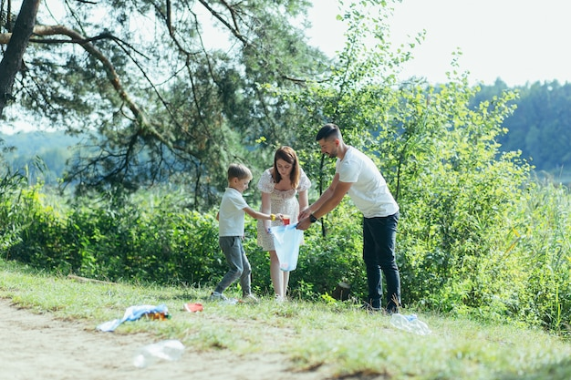 Family volunteer cleans garbage in nature. father and mother, parents, children, son family volunteers in a sunny day cleaning up the rubbish waste bottles in forest of debri folding in plastic bag