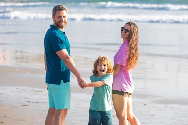 Семейная прогулка по морскому пляжу. счастливые родители с ребенком, играющим на пляже. проведение летнего времени на природе.