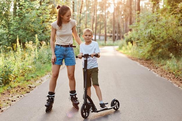 여름날 가족 산책과 휴식, 롤러 스케이트를 타는 엄마와 아들 스케이트를 타는 레크리에이션 공원에서 스쿠터를 타고 활동적인 방식으로 시간을 보내고 건강한 라이프 스타일을 보냅니다.