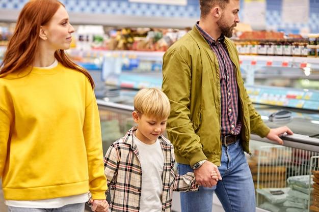 Семейная прогулка в супермаркете, кавказские родители, держащиеся за руки своего сына, наслаждаются покупками
