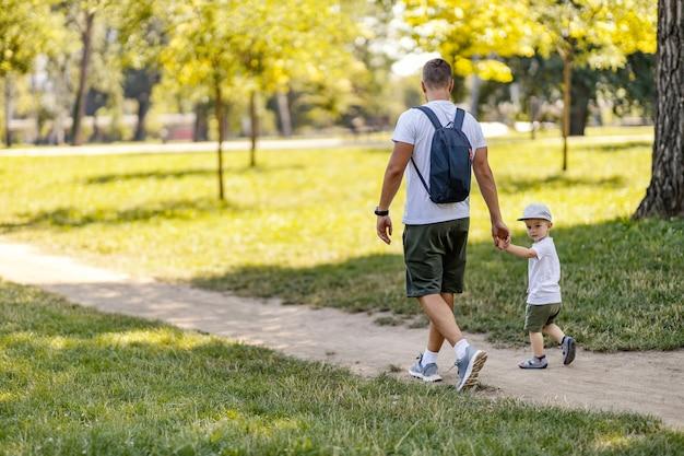 家族は森の中を歩きます。お父さんは男の子の手を握り、晴れた夏の日に二人は森の中を歩きます。同じカジュアルスーツを着た男の子の後ろからのショット。自然界の家族