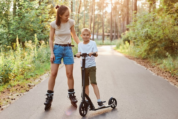 Family walk and rest in the summer day, mom riding roller skates and her son skates on a scooter in a recreation park, spending time in active way, healthy lifestyle.