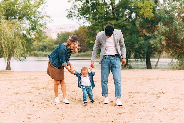 湖の近くの公園の砂の上を歩いて一緒に楽しい時間を過ごす家族