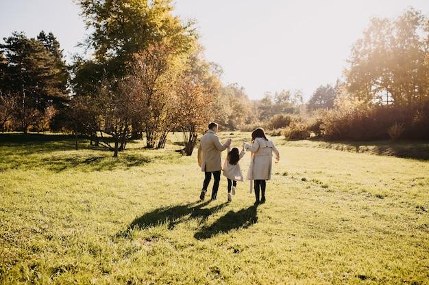 公園を散歩する家族暖かい春の日に手をつないで楽しんでいる父母と娘