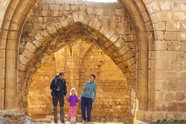 古いヨーロッパの町の通りを歩いている家族