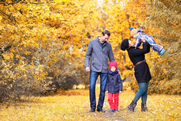 Family walking with children in autumn park in the afternoon