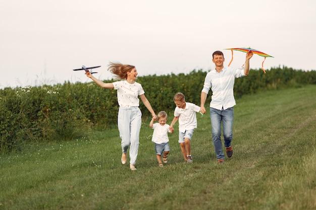 La famiglia cammina in un campo e gioca con l'aereo giocattolo