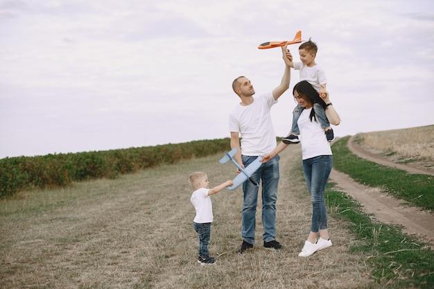 家族がフィールドを散歩し、おもちゃの飛行機で遊んで