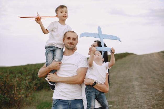 Семья гуляет в поле и играет с игрушечным самолетиком