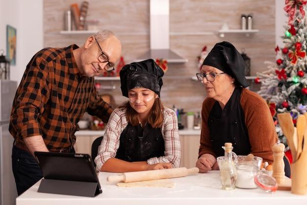 テーブルに立っているタブレットでオンライン料理のレッスンを見ている家族