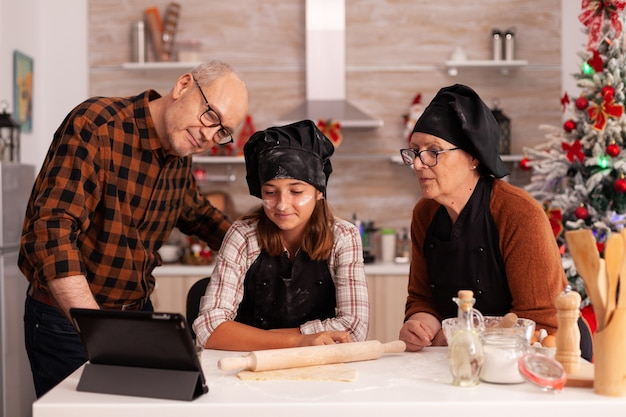 Family watching online cooking lesson on tablet standing at table