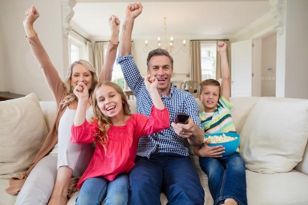リビングルームのテレビでサッカーの試合を見て家族