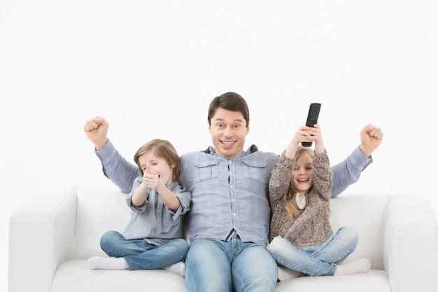 Семья смотрит телевизор вместе на диване