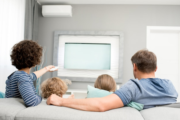 Family watching tv, back view