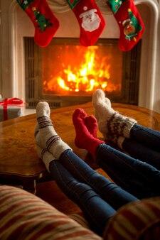 燃える暖炉のそばに座ってニットの靴下を履いている家族