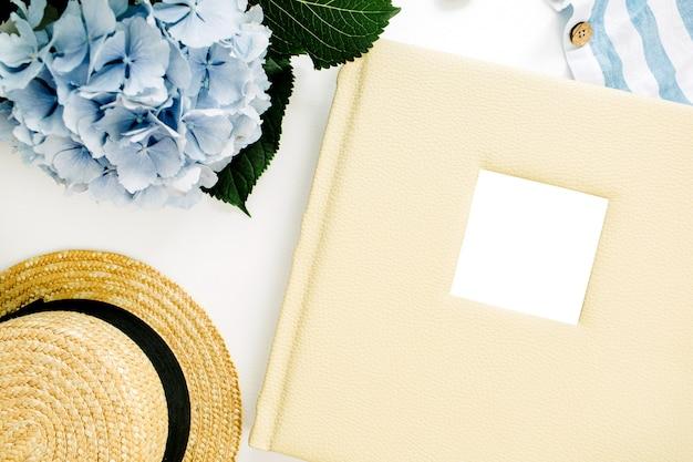 家族の結婚式の写真アルバム、青いアジサイの花の花束、縞模様の毛布、麦わら帽子、白い表面の装飾