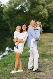 家族の週末。小さな息子と娘と美しい若い家族が屋外で歩く