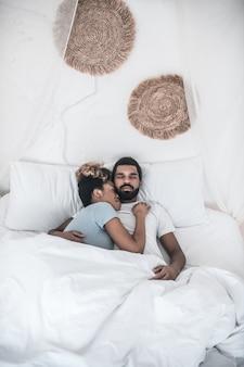 家族、幸福。若いアフリカ系アメリカ人の女性と寝室で休んで抱き締めて横になっている目を閉じた男