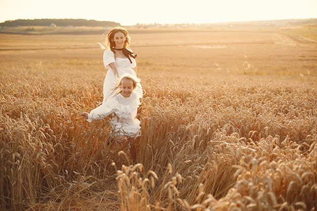 Family in a wheat field. woman in a white dress. girl with straw hat.