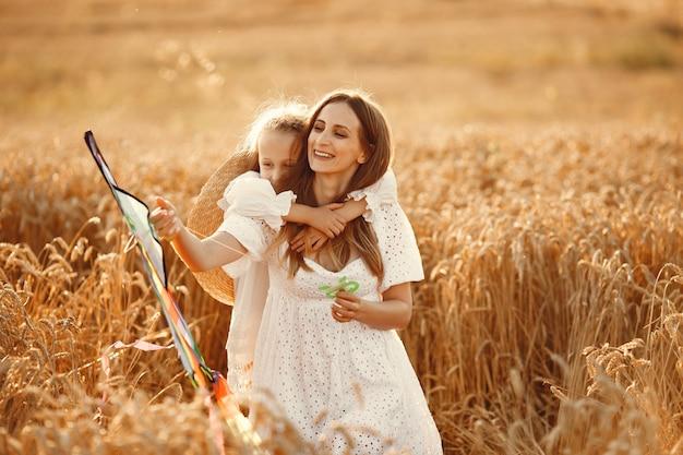 Famiglia in un campo di grano. donna in abito bianco. piccolo bambino con l'aquilone.