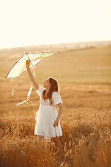 Family in a wheat field. woman in a white dress. little child with kite.
