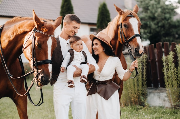A family in white clothes with their son stand near two beautiful horses in nature. a stylish couple with a child are photographed with horses.