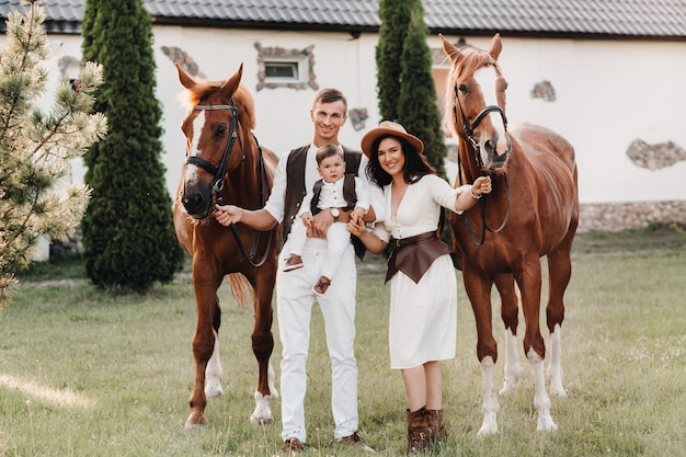 A family in white clothes with their son stand near two beautiful horses in nature