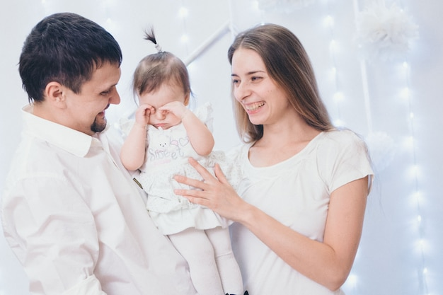 Family  on a white , parents spend time with their children. mom and dad hug the baby.  childhood, fatherhood, motherhood, ivf