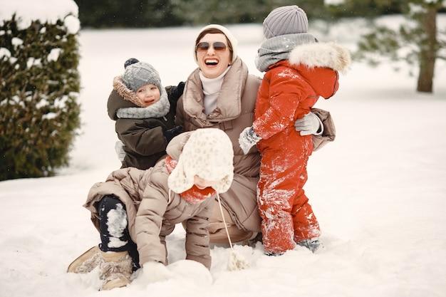 Famiglia in abiti invernali in vacanza nel bosco innevato