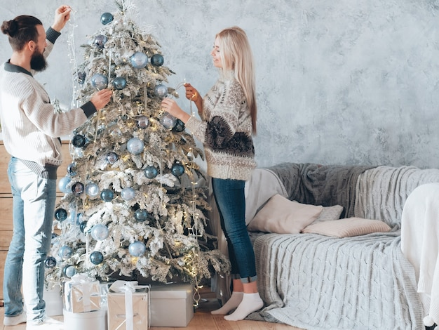 가족 겨울 방학. 요정 조명으로 전나무 트리를 장식하는 행복 한 커플.