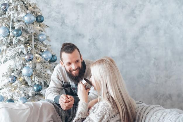 가족 겨울 방학. 따뜻한 대화를 나누는 행복 한 커플. 아늑한 축제 홈 인테리어 공간을 복사합니다.