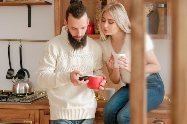 가족 겨울 아침 레저. 크리스마스 파티 초대장을 보내기 위해 스마트 폰을 사용하여 부엌에서 커피를 마시는 커플.