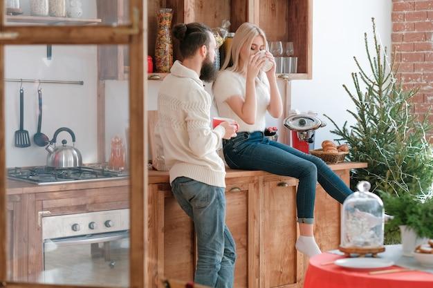 가족 겨울 아침 레저. 나무 가구와 현대 부엌에서 커피를 마시는 커플
