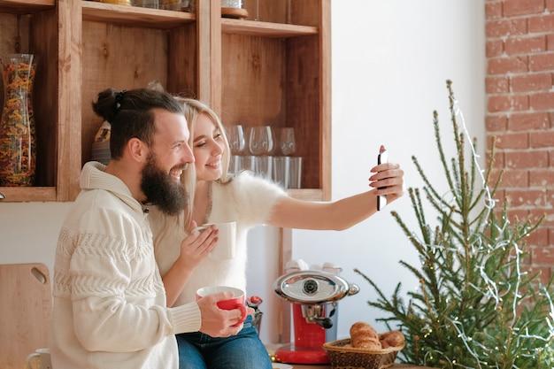 가족 겨울 아침 레저. 커피를 마시는 커플, 스마트 폰 카메라를 사용하여 현대 부엌에서 셀카를 찍습니다.