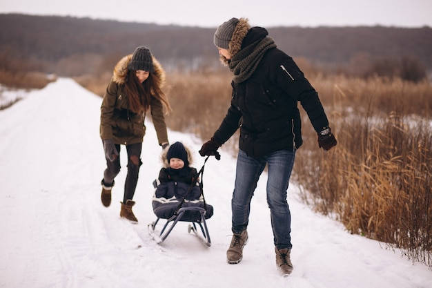 Family in winter with son sledging