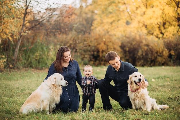 Семья с ребенком и двумя золотистыми ретриверами в осеннем парке