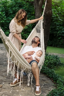 ハンモックで男の子の赤ちゃん連れの家族が、優しくて優しい父性を満たしています。お父さんの膝の上にかわいい息子