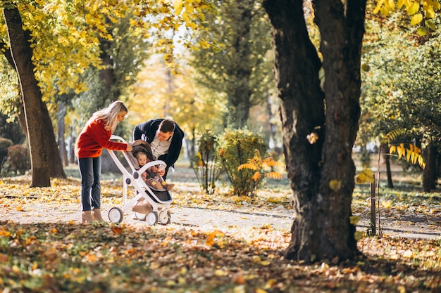 Family with baby daugher in a baby carriage walking an autumn park