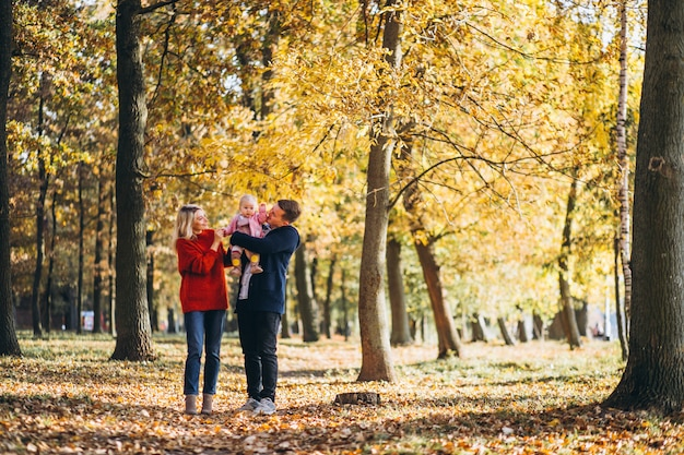 Family with baby daugher walking in an autumn park