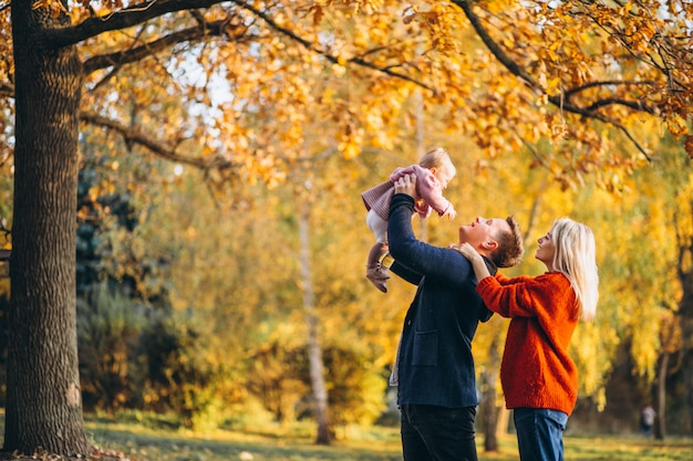 Family with baby daughter walking in an autumn park