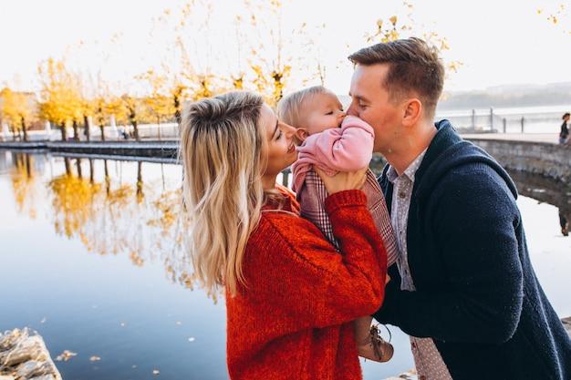 公園を歩いている赤ん坊の娘と家族